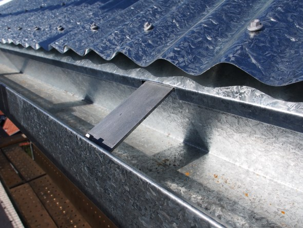 Secured from the top with flashing installed to prevent rain blowing in beneath the corrugations.