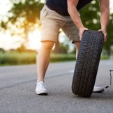 The man changes the tire to a broken car on the road