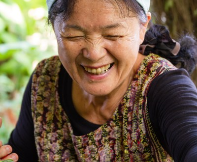 Okinawan woman laughs while picking Greens