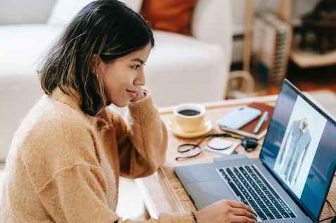 smiling ethnic remote worker using laptop with photo on screen