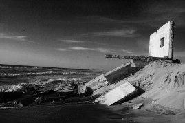 Klimatförändringarna; det stigande havet, blir som allra synligast intill stranden. Här erroderas marken fort och det som en gång var det perfekta strandhuset är nu bara en vägg. Vid nästa storm är också den borta.
