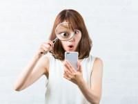 スマホを虫眼鏡で見る女性