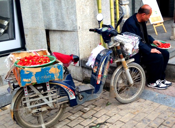 China: This man sells strawberries on the back of his bike in the same spot every day. #XianScenes #Chinalife
