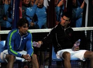 Novak Djokovic of Serbia (R) offers water to Rafael Nadal