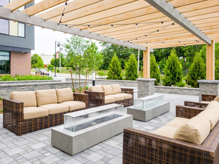 Pergola patio space with gas fireplaces, couches, and overhead lights