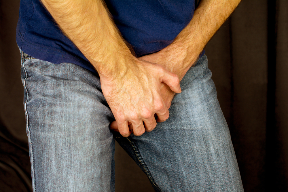 man holding hands in front of his pants
