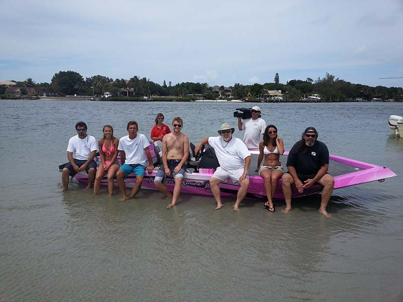 group of people sitting on a pink boat on a lake