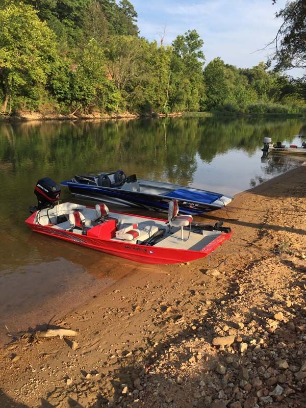 three boats lined up on gravel bar