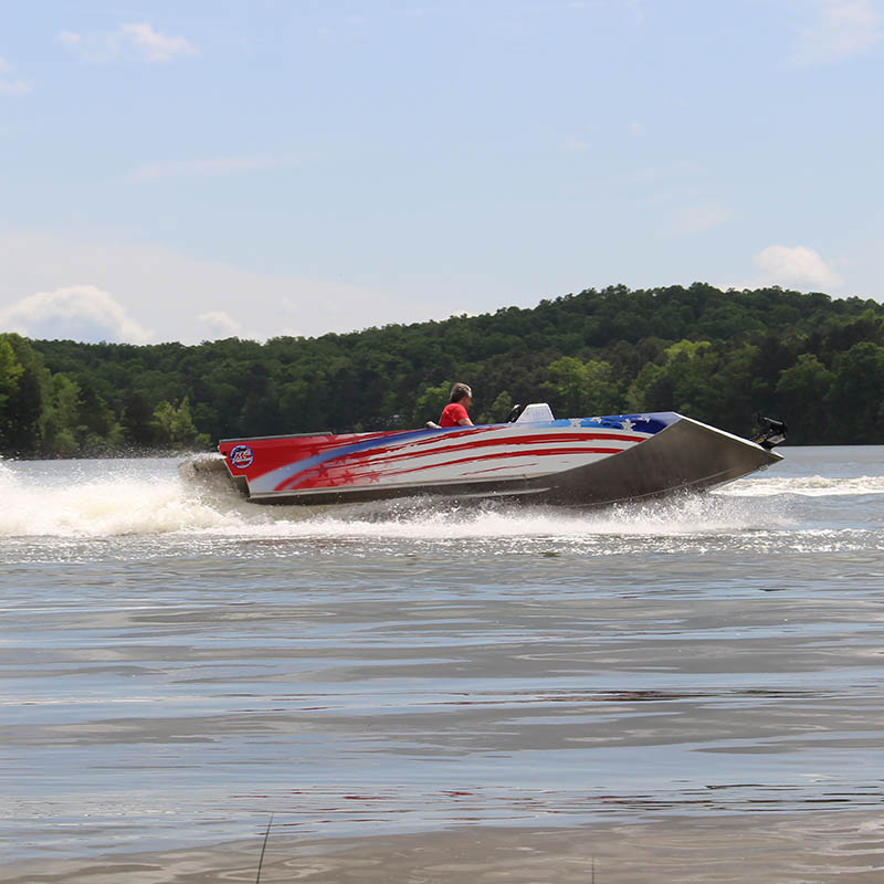 man driving a red, white, and blue speedboat