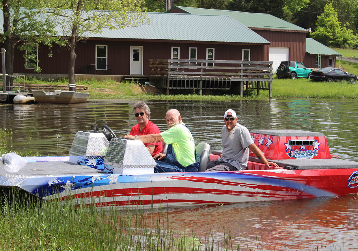 three men in a red, white, and blue boat