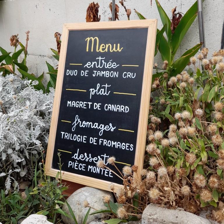 Menu calligraphié sur ardoise pour un mariage aux tons de blanc et doré, placé dans un jardin
