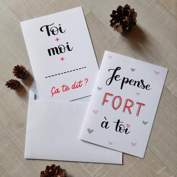 """2 modèles de cartes romantiques pour la Saint Valentin, calligraphiées et imprimées à Toulouse. Les deux cartes sont dans les tons noir et rouge sur fond blanc. L'une dit """"Toi + moi + ... Ça te dit ?"""" et l'autre dit """"Je pense fort à toi"""""""