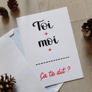 """Carte de St Valentin à commander, avec message à compléter """"Toi + moi + champ libre. Ça te dit ?"""". Le message est écrit en tons de noir et rouge sur fond blanc et suggère une invitation à une activité ou un endroit via le champ qui est laissé libre à l'expéditeur pour compléter.."""