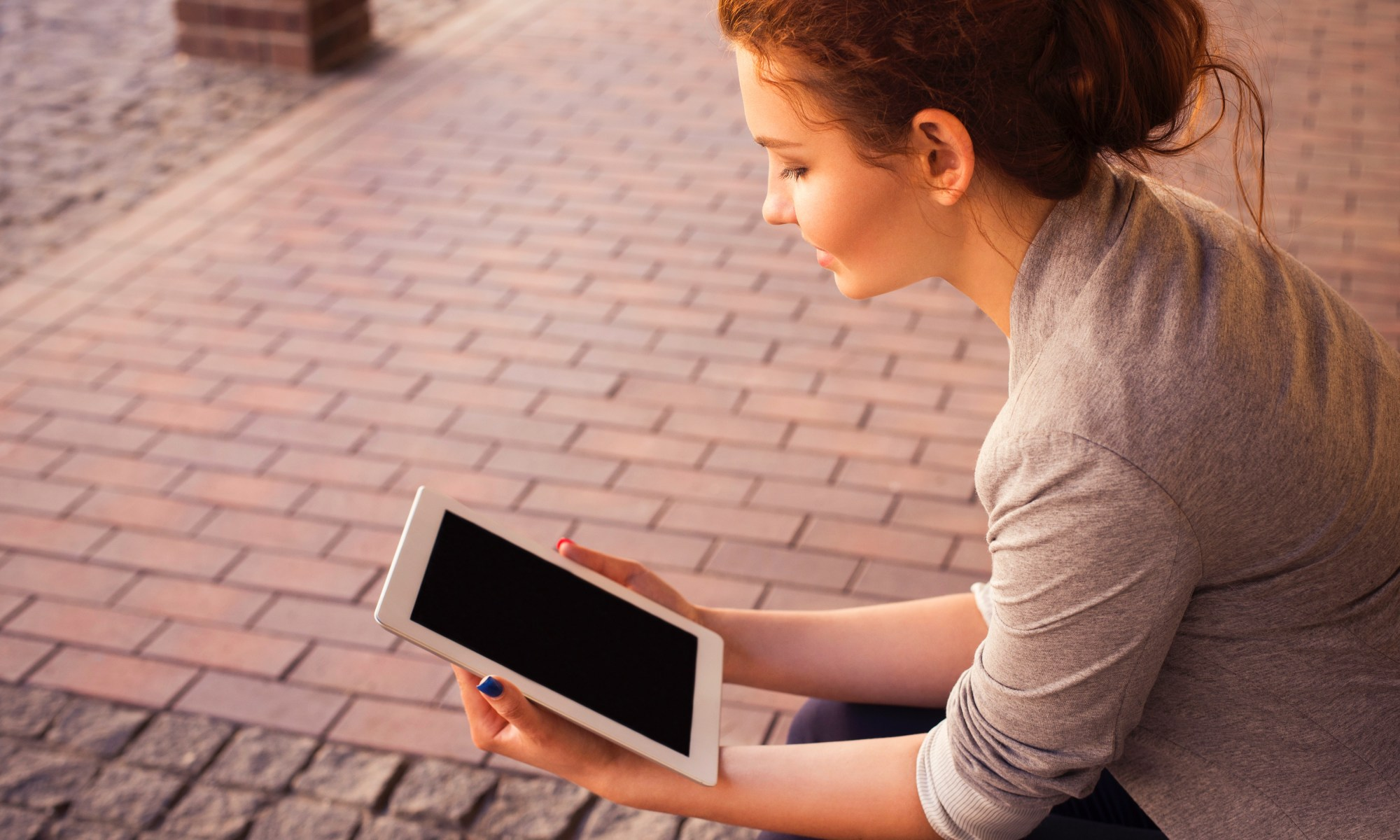 Young woman on sidewalk with tablet
