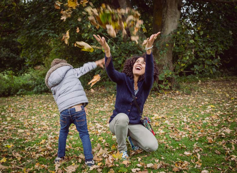 Enfield photographer - documentary lifestyle photography family in the park, mum and son throwing leafs, enjoying each others company, in London, South East England