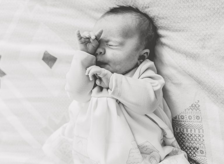 newborn baby girl having a stretch in b&w on the bed photographed by London family photographer