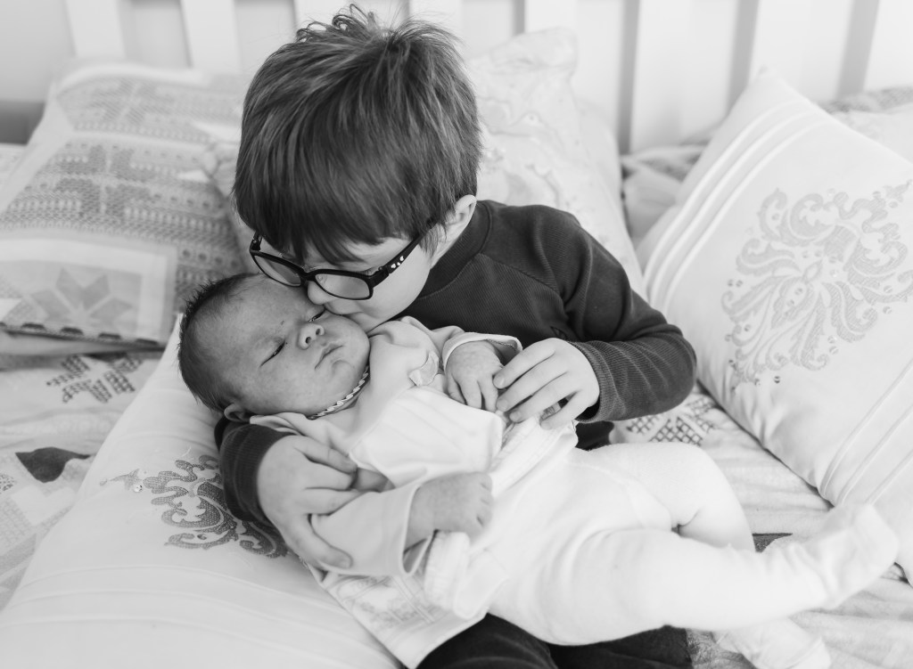 what happens at the home lifestyle photoshoot b&w newborn girl and sister kissed by hier brother