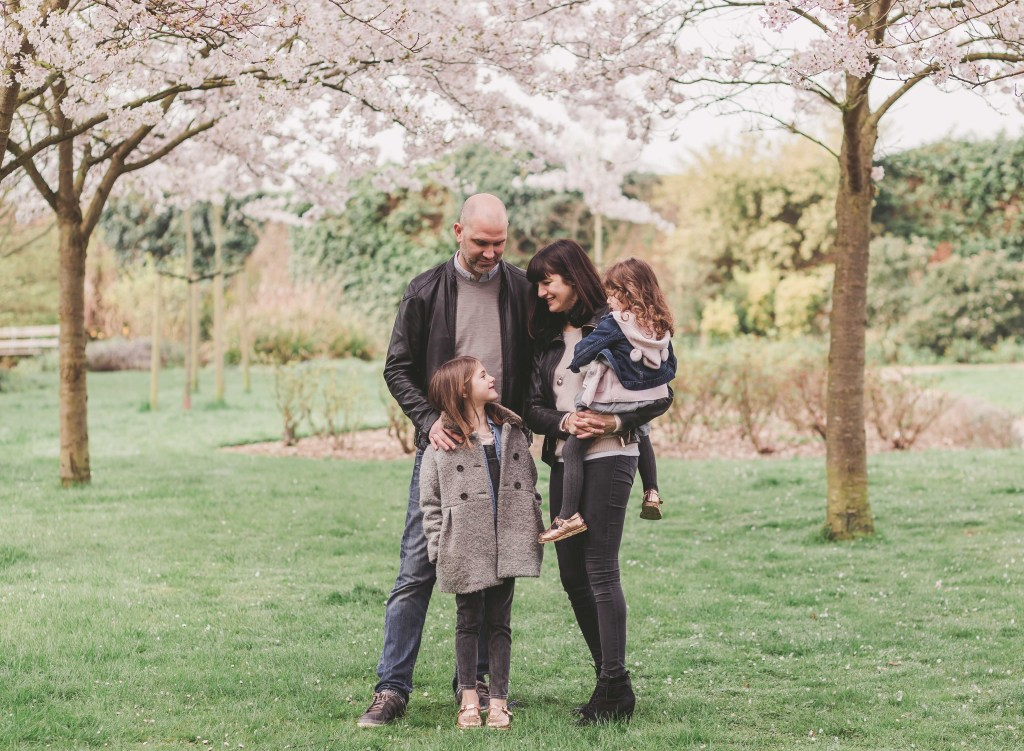 family photoshoot mum dad daughters cuddling in the park under the trees outdoor photoshoot in London Enfield photographer