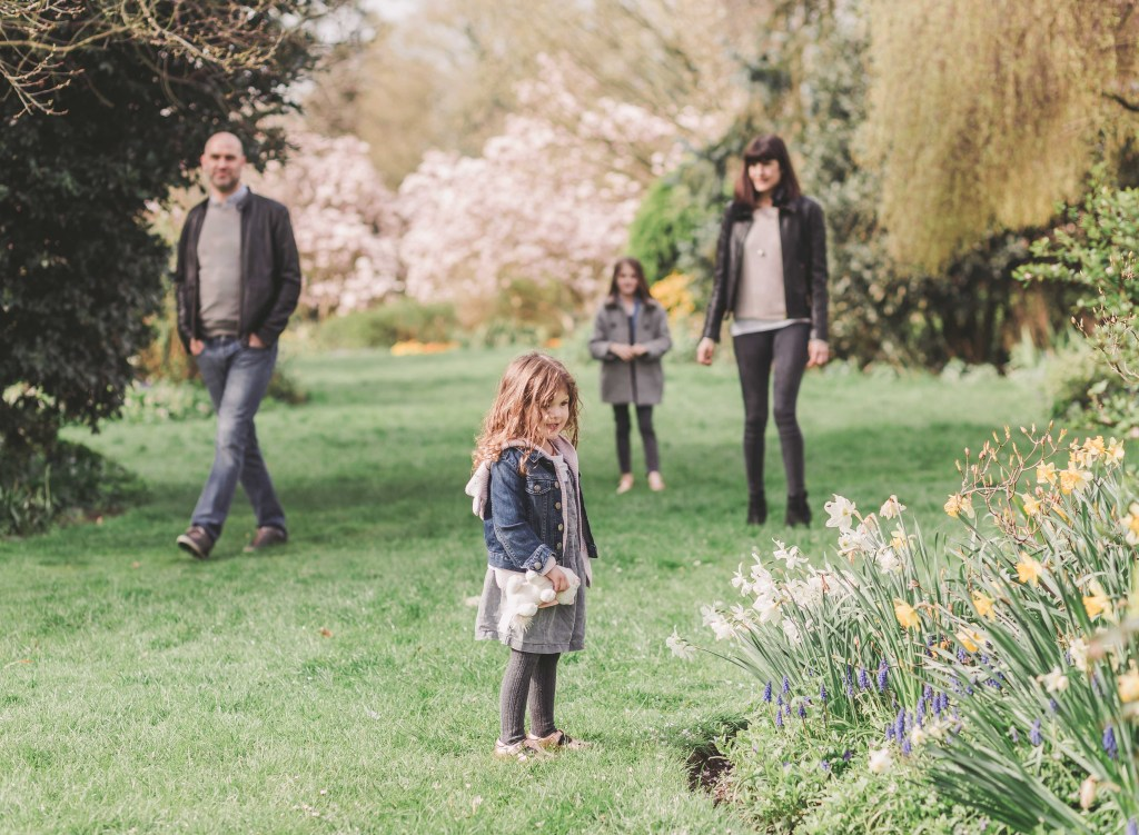 daughter is looking at the bee on the flower mum dad sister looking at the girl in the background of Forty Hall Enfield London family photographer