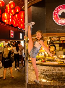 dancing gymnastics standing on one foot near the food of Camden market of Camden Town London family photographer