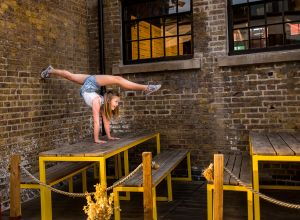 dancing gymnastics handstand on the table Camden market of Camden Town London family photographer