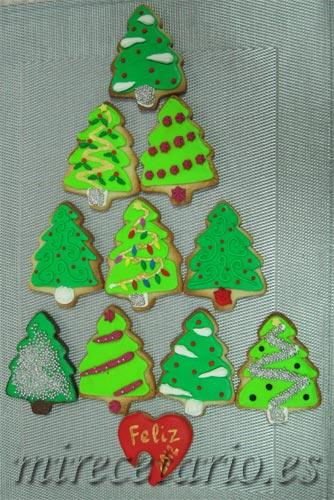 Variedad de galletas decoradas con forma de árbol de navidad.