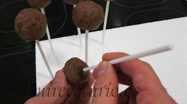 Clavando el palito untado en chocolate fundido.