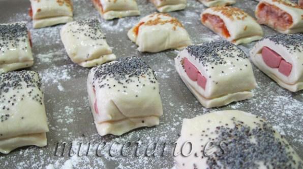 Saladitos hot dog y saladitos de atún listos para entrar en el horno.