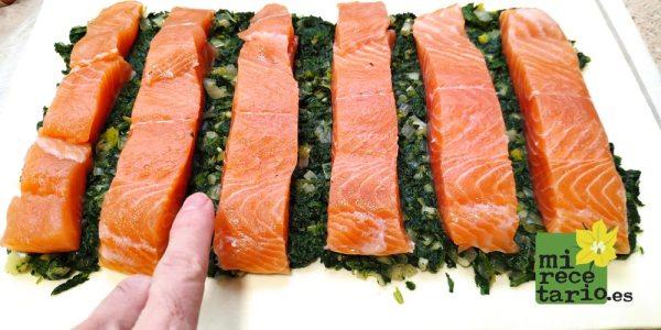 El salmón sobre las espinacas separado 1 centímetro.