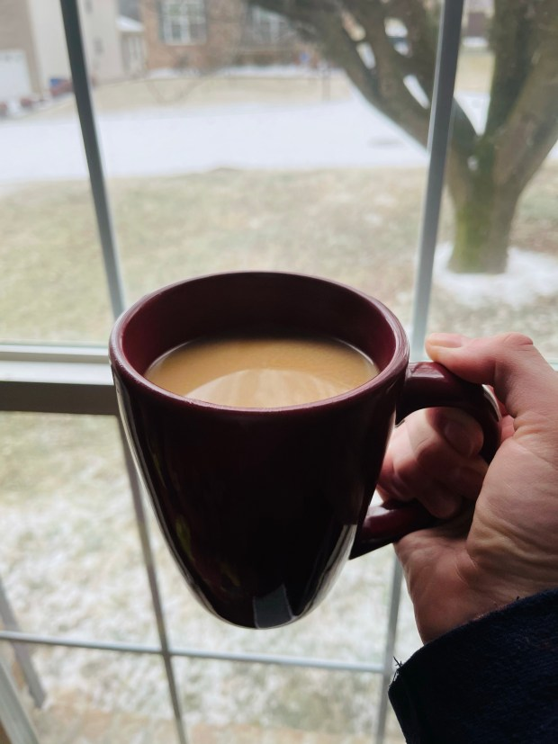 Cup of coffee by window with snow