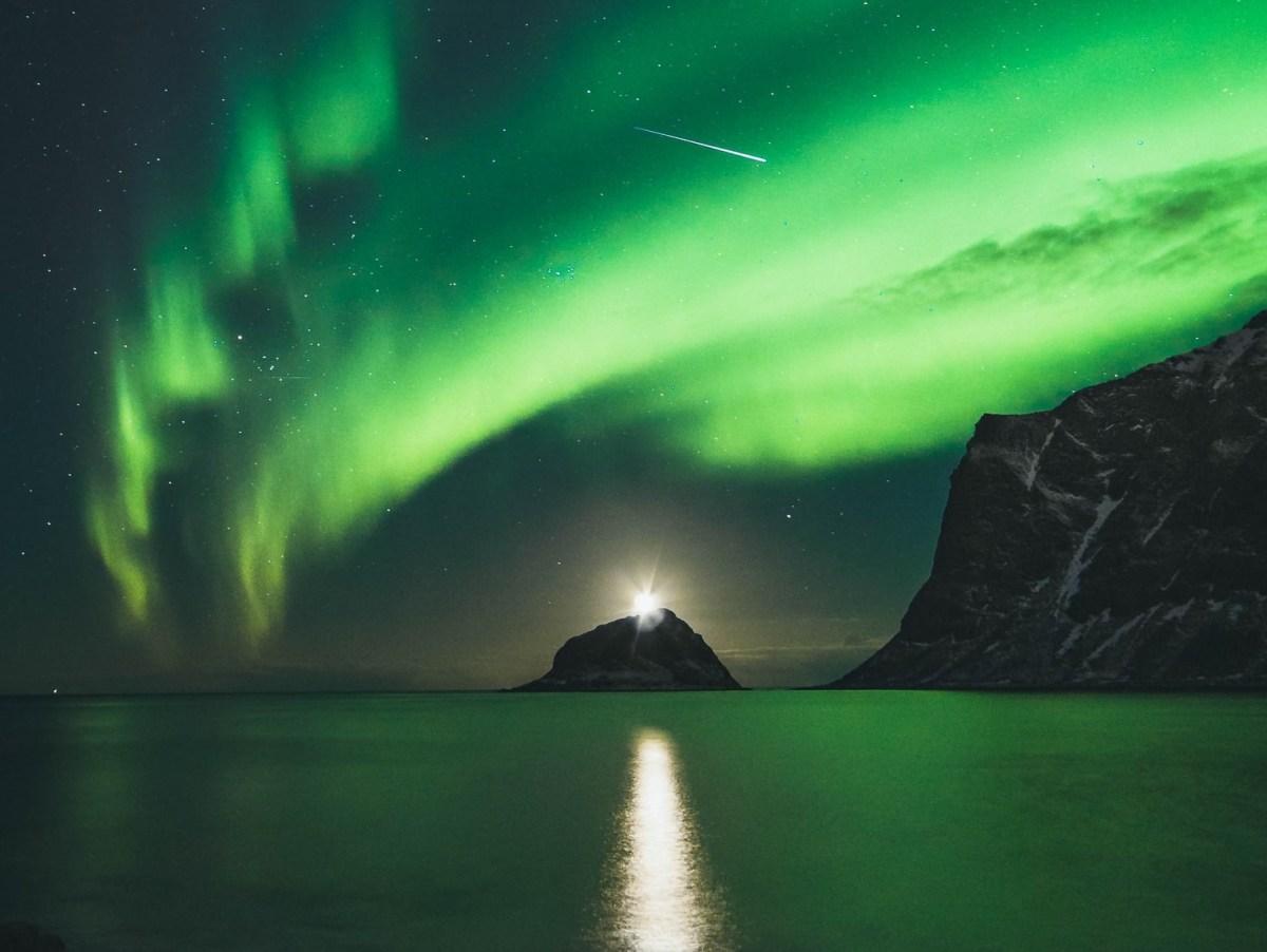 Nascer do Sol em meio ao cenário da Aurora Boreal com uma estrela cadente