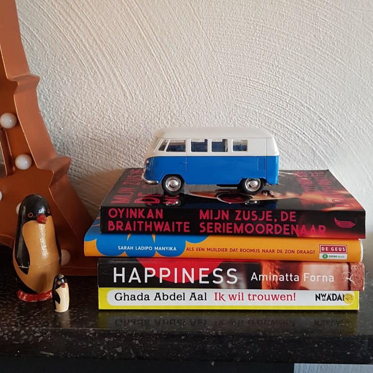 Op een zwarte marmeren plaat ligt een stapel van 4 boeken. Bovenop de stapel staat een blauw speelgoedbusje, een Volkswagen. Naast de stapel staat een Eiffeltoren en 2 houten pinguins.