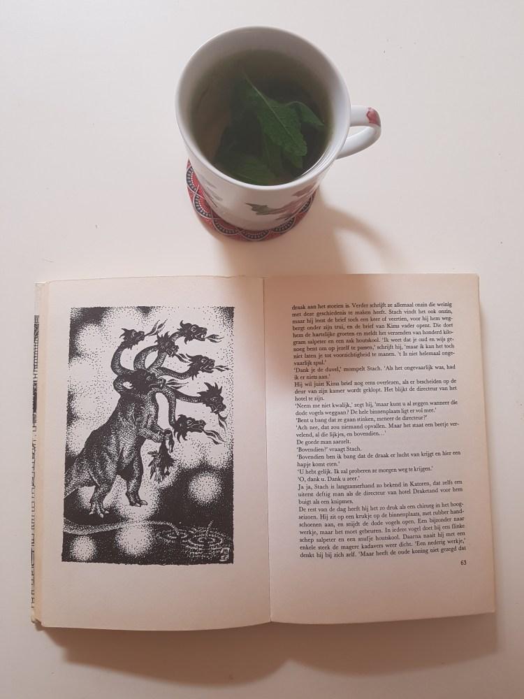 Op een witte achtergrond ligt een vergeeld boek, opengeslagen. Op de linkerpagina staat een pentekening van een draak 7 hoofden. Op de rechterpagina staat tekst. Boven het boek staat een mok muntthee.