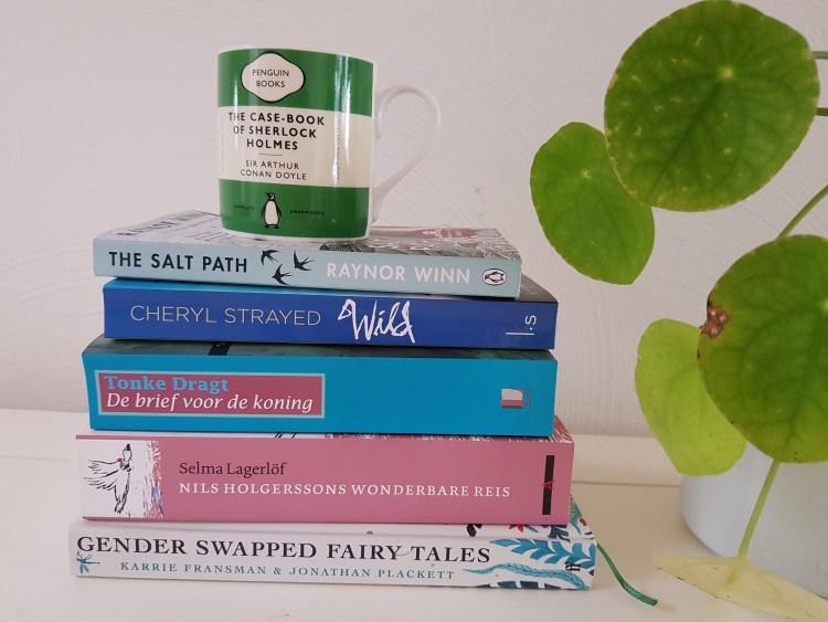 Op een witte tafel ligt een stapel van 5 boeken. Op het bovenste boek staat een groen/witte mok van Uitgeverij Penguin. Naast de stapel staat een pannenkoekenplant, 4 bladeren ervan zijn zichtbaar.