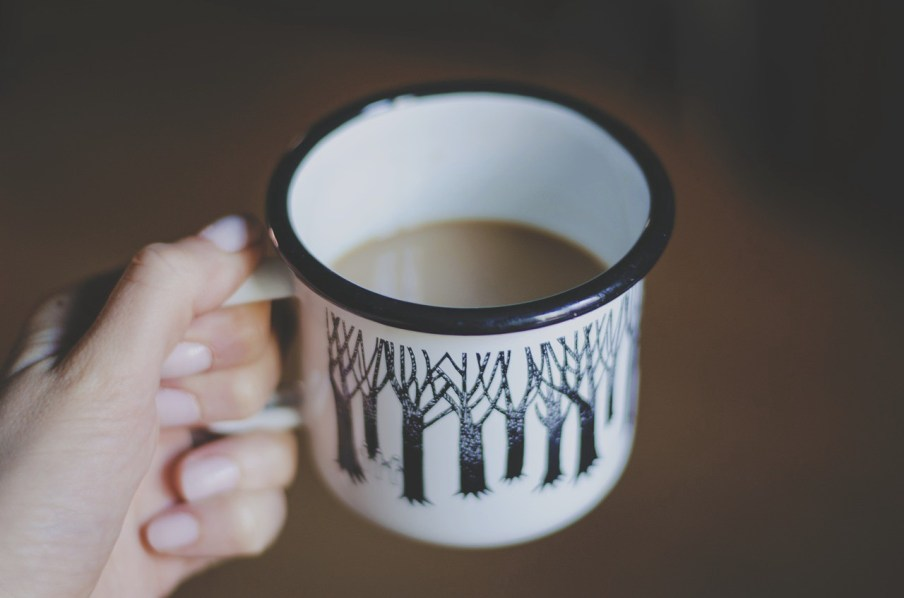 A hand holds a coffee cup half-full of coffee. Or is it half empty? You decide.