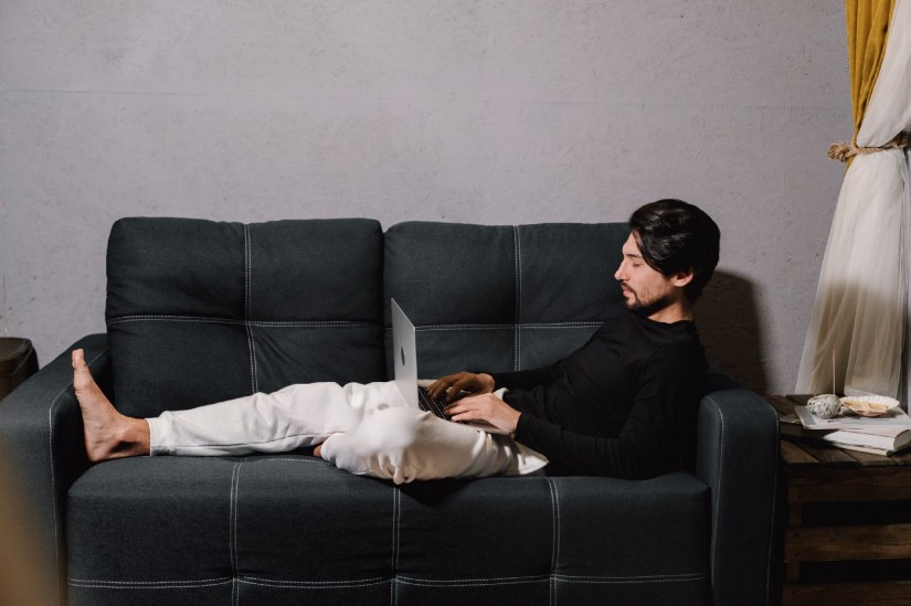 Man typing on a laptop while lying on a sofa.