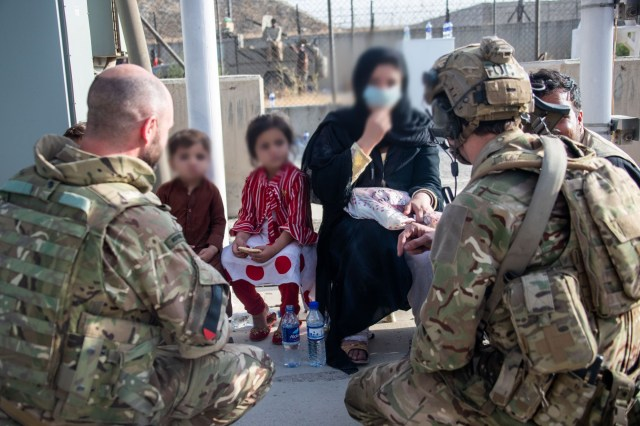 Personnel interact with a family at Kabul International Airport.