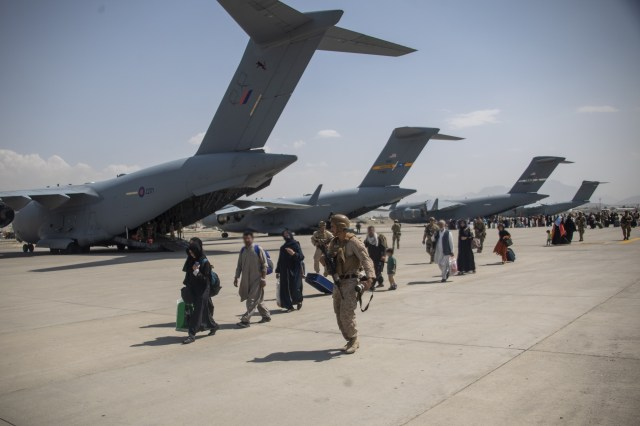 Afghan civilians head towards a plane ready to take them out of Afghanistan.