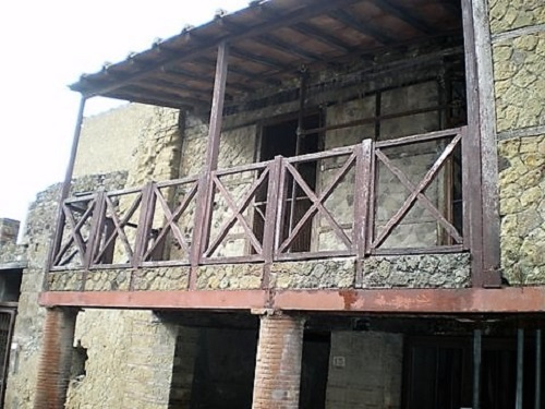Casa de dos plantas con barandilla de madera en Herculano