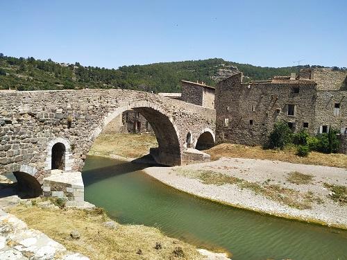 Puente viejo de piedra con 3 arcos asimétricos