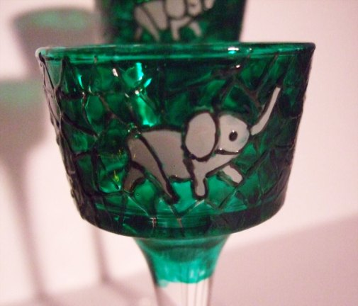 Three small grey elephants with a green background.