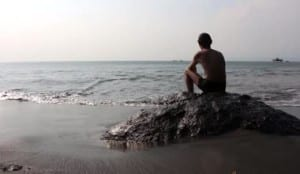 depositphotos_71276367-Man-Sitting-on-the-Rock-and-Looking-at-the-Sea-1