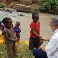 Padre João Henrique brinca com crianças perto do rio.