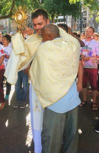 Padre Leandro com o Santíssimo Sacramento é abraça uma pessoa