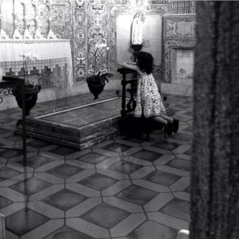 Criança ora de frente ao sacrário.