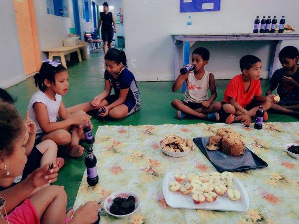 Crianças comem o lanche oferecido pelo Oratário