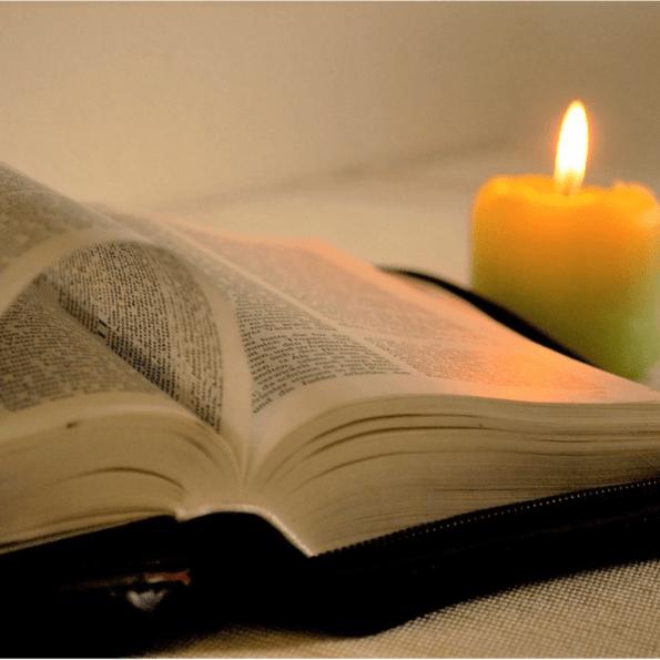 Bíblia aberta com vela do lado