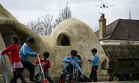 Pupils of Hounslow Heath school play around the huts in the playground as another low jet flies in