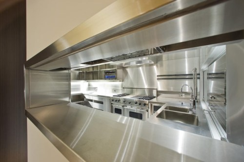 Contemporary-House-with-Completely-Stainless-Steel-Kitchen-with-kitchen-island-sink-oven-stove-cabinet-table-refrigerator-hood