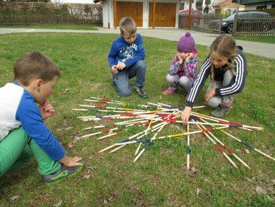 niños jugando a mikado en el jardin